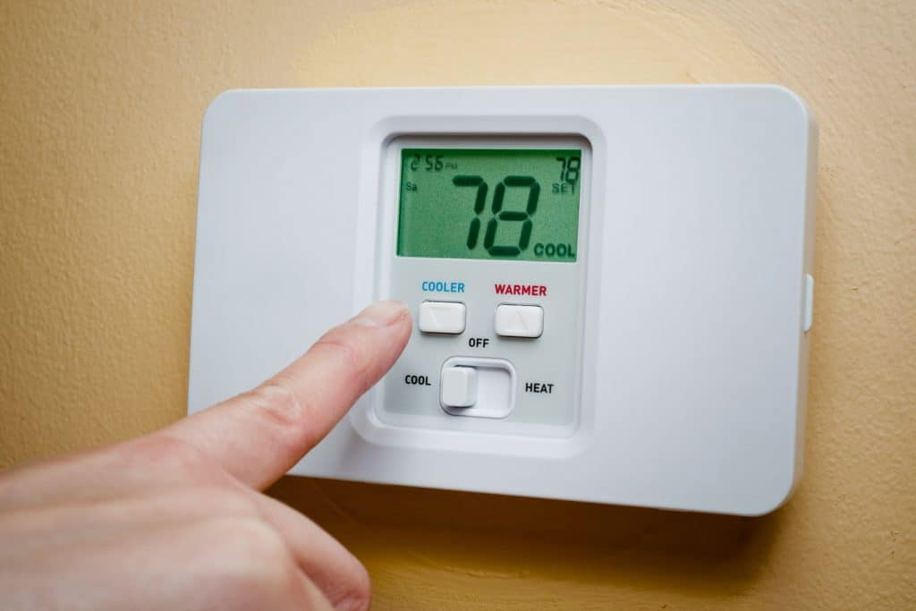 A woman setting her thermostat to a cooler temperature
